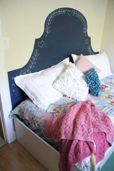 Modern girl's platform bed with headboard painted on wall
