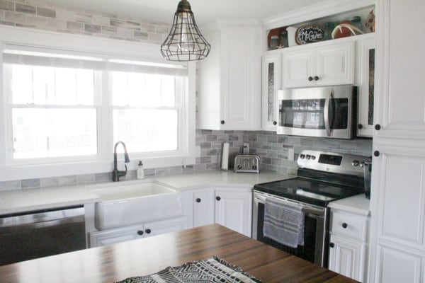 Kitchen with white counters and grey backsplash
