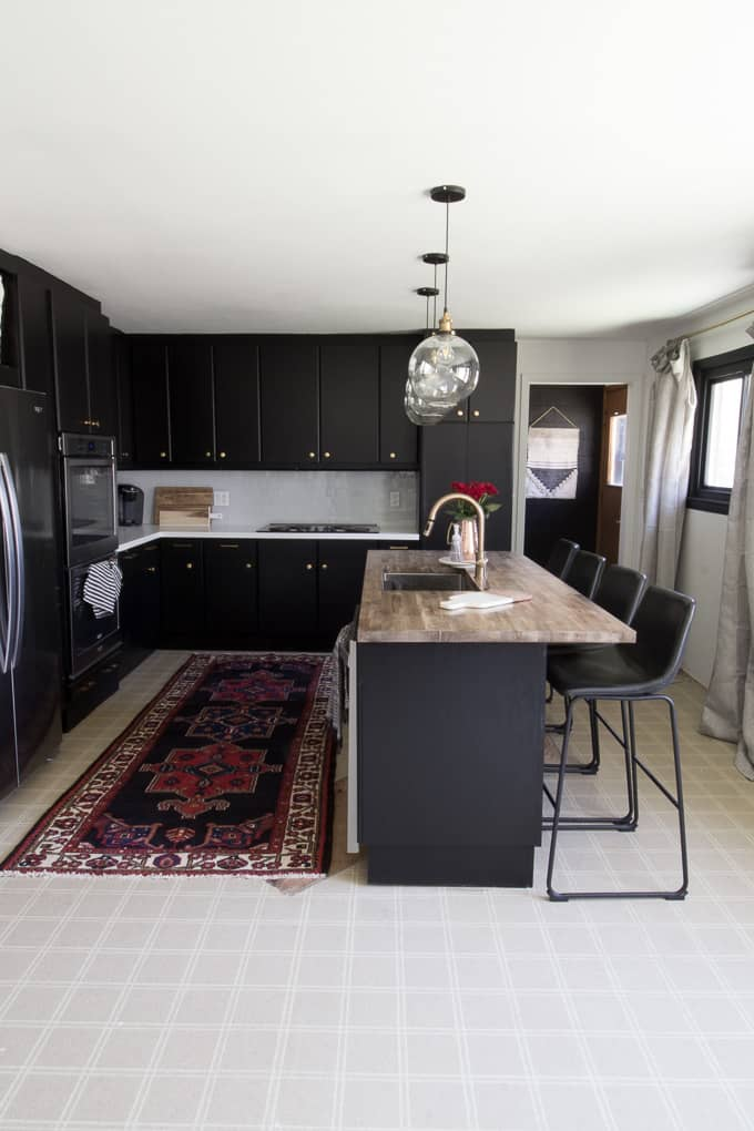 Kitchen With Black Cabinets And Butcher Block Countertops