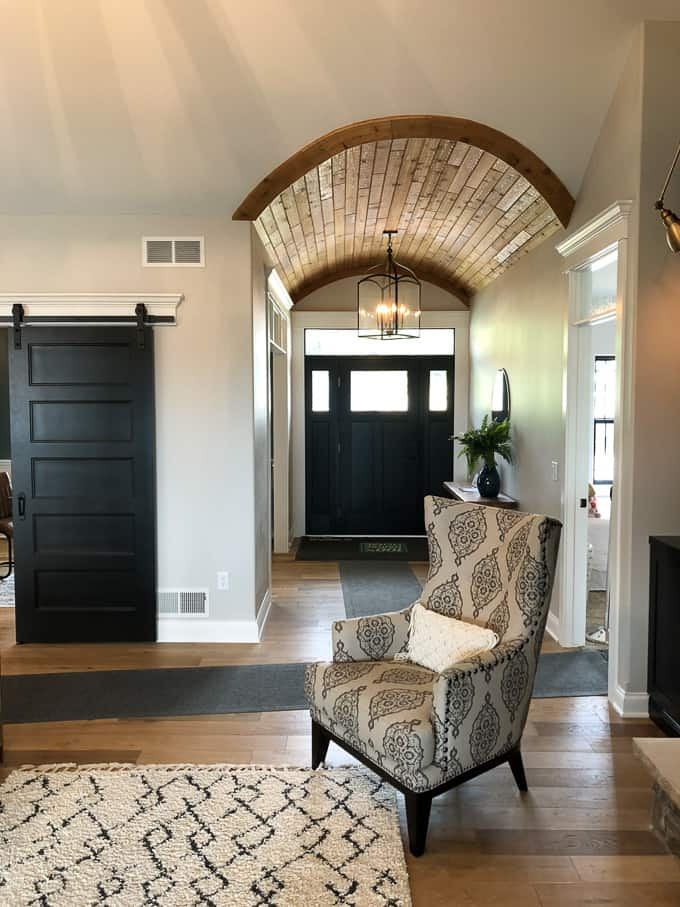 Arched Entryway with Wood Ceiling and Black Front Door