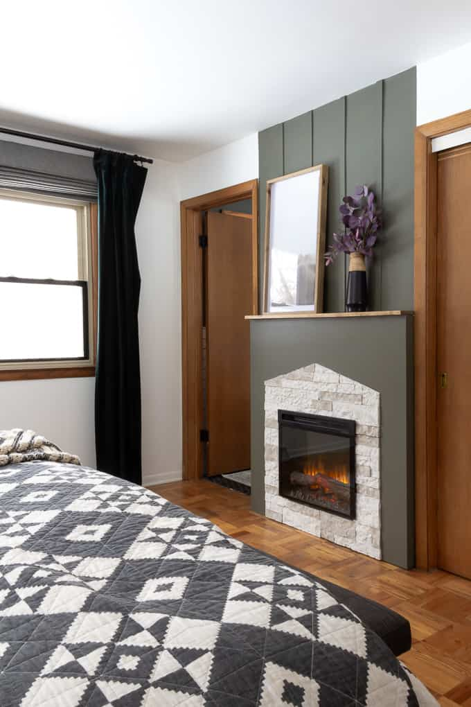 Bedroom with Electric Fireplace with Green and Airstone Fireplace Surround